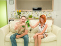 Friends toasting with beer front view of men and women sitting on couch bottles Stock Photography