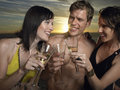 Friends toasting champagne outdoors young people in bathing suits at sunset Stock Photos