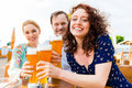 Friends toasting in garden restaurant with beer Royalty Free Stock Photo