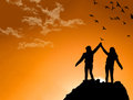 Friends on top of a mountain shaking raised hands at sunset Stock Images