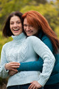 Friends two young women brunette and redhead laughing and hugging Stock Images