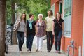 Friends walking together on pavement full length of Stock Image