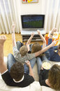 Friends watching football match and celebrating rear view of young in living room Royalty Free Stock Images