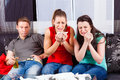 Friends watching a sad movie in tv man an two women Royalty Free Stock Image