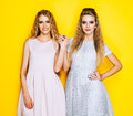 Friendship forever. Two stunning blonde girl in beautiful dresses are friends and they raised their hands. Indoor. Royalty Free Stock Photo