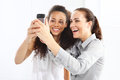 Friendship friends learn to read message two women take pictures with your phone Stock Image