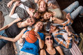 Friendship, leisure, summer and people concept - group of smiling friends lying on floor in circle indoors Royalty Free Stock Photo