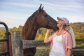 Friendship woman and horse special bonding moment between at split rail fence outdoor at ranch in virginia Royalty Free Stock Image
