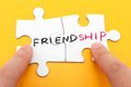Friendship word written on two pieces of puzzle Royalty Free Stock Photos