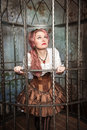 Frightened beautiful steampunk woman in the cage with pink hair standing metal Royalty Free Stock Photos