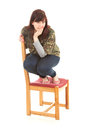 Frightened fat teenage girl on chair, full length Stock Image