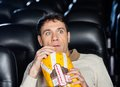 Frightened man watching movie in theater eating popcorn while cinema Stock Photo
