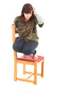 Frightened overweight young woman on the chair Stock Photo
