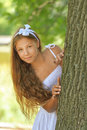 Frightened teenage peeping from behind tree beautiful against green of summer park Royalty Free Stock Photography
