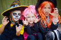 Frightening girls portrait of three little in halloween costumes looking at camera with gesture Stock Image