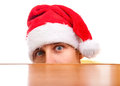 Frightful young man in santa hat behind the table on the white background Royalty Free Stock Photography