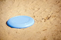 Frisbee lying in sand a blue disc on the of beach Stock Photos
