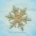 Frohe weihnachten merry christmas in german picture of a golden snowflake shaped star on the snow and the sentence with Royalty Free Stock Image