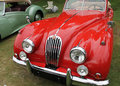 Front classic jag xk convertible vintage red jaguar drophead coupe sports car view next to vintage healy sports car Royalty Free Stock Photo