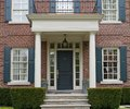 Front door of house with porch portico style Stock Images