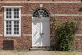 Front door transom windows and climbing rose at a typical brick entrance in historic building of red with white in northern Stock Photos