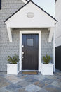 Front door of an upscale home vertical shot a black with view sky plants and roofline Royalty Free Stock Photo