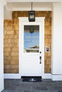 Front door of an upscale home vertical shot a white with a reflection in the window and view anchor mat and wooded Royalty Free Stock Photography