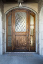 Front door of an upscale home vertical shot a wooden on with large frosted glwoing windows and view mailbox mat and light Stock Photos