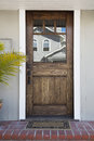Front door of an upscale home vertical shot a wooden with reflection in the windows and view doormat brick flooring and palm Royalty Free Stock Photos
