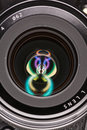 Front element of a camera lens macro shot with beautiful color lights reflections Royalty Free Stock Photo