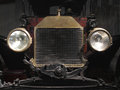 Front end of a vintage car close up view very early showing brass radiator and large headlights Royalty Free Stock Photo