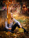 In front of graffiti sitting amongst the leaves.