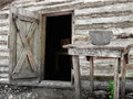 Front of an old log shack close up the with open door and outside table with a metal pot Royalty Free Stock Photo