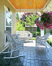 Front porch with white furniture and flowers. Stock Photo