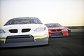 Front view of auto racing race cars racing on a track with motion blur room for text or copy space Stock Photos