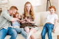 Front view of beautiful redhead family playing with puppy at home Royalty Free Stock Photo