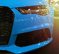 Front view of blue modern luxury sport with soft orange sun light. Car exterior details. Headlight of a modern sport car. Royalty Free Stock Photo