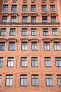 Front view of brick wall contemporary apartment building with windows Royalty Free Stock Photo