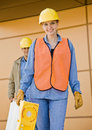 Front view of construction workers carrying ladder Stock Photography