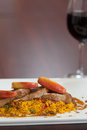 Front view of couscous dish with meat and red wine on wooden table Royalty Free Stock Photography
