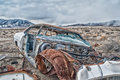 Front view of an old abandoned car and parts in the desert Royalty Free Stock Photo