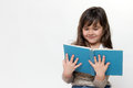 Front view of smiling little girl reading a book Royalty Free Stock Photo