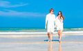 Front view of young happy caucasian couple in white walking on beach looking at the sea this image has attached release Royalty Free Stock Photos