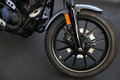 The front wheel of a motorcycle and fender on black floor Stock Image
