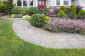 Front yard garden curve paver path brick with green grass lawn flowering plants trees and shrubs Stock Photos