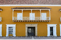 Frontal view of yellow house with white doors, window and balcony Royalty Free Stock Photo