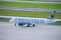Frontier airlines plane on the airport tarmac a is taxiing down runway at an Royalty Free Stock Photo