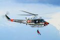 Frontier guard helicopter agusta bell flying over sea with rescuer man ready to help Stock Image