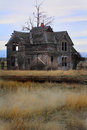 Frontier homestead an abandoned desolate house dead trees and prairie grasses shallow depth of field Royalty Free Stock Images