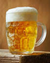 Frosty glass of light beer on wooden board Stock Photo